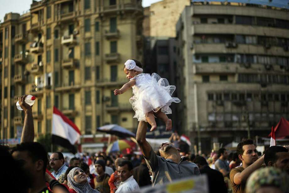"TOPSHOTS An Egyptian man carries his daughter in Egypt's landmark Tahrir square on July 4, 2013. Egypt's Muslim Brotherhood, from which ousted president Mohamed Morsi hails, denounced a new ""police state"" after the arrest of Islamist leaders and the closure of satellite channels. TOPSHOTS/AFP PHOTO/GIANLUIGI GUERCIAGIANLUIGI GUERCIA/AFP/Getty Images Photo: GIANLUIGI GUERCIA / AFP ImageForum"
