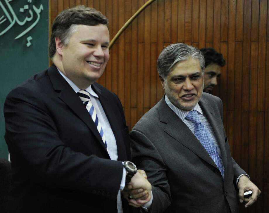 Pakistani Finance Minister Ishaq Dar (R) shakes hands with International Monetary Fund (IMF) Pakistan Mission Chief Jeffrey Franks in Islamabad on July 4, 2013. Pakistan on July 4 asked the IMF Fund for a USD 5.3 billion, three-year loan to boost growth in a bid to rebuild foreign exchange reserves, an energy crisis and a sliding currency. AFP PHOTO / AAMIR QURESHIAAMIR QURESHI/AFP/Getty Images Photo: AAMIR QURESHI / AFP