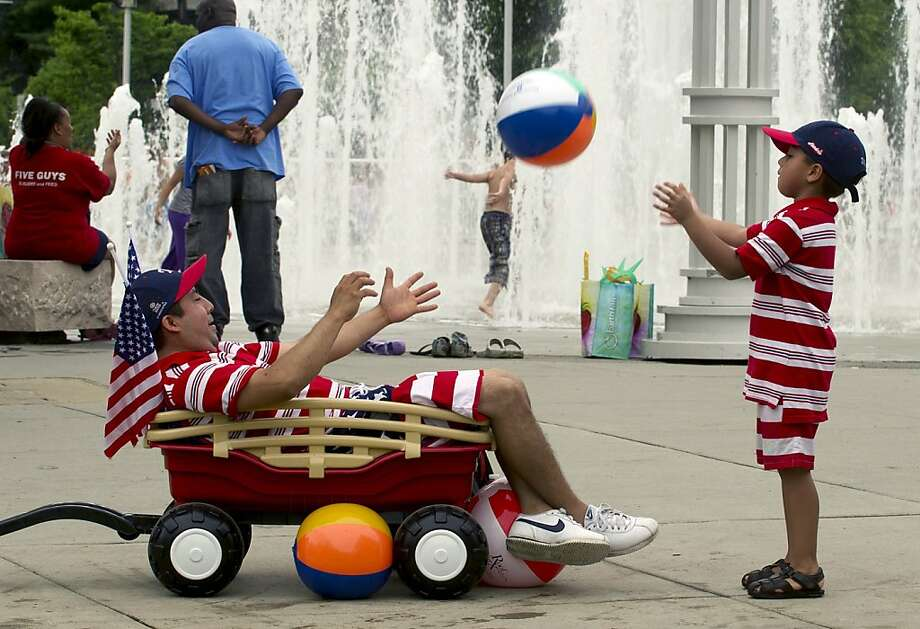 Bruno Albarran, left, and his son, Abishai, play catch during Festival on the Fourth festivities at World's Fair Park on Thursday, July, 2013, in Knoxville, Tenn. Photo: J. Miles Cary, Associated Press