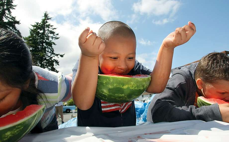 Alex Antoni,7, of Keyport has a unique way to not use his hands during the watermelon eating contest at the Keyport Independence Day festivities Thursday, July 4, 2013. Photo: Larry Steagall, Associated Press