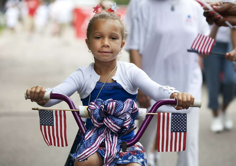 Maya Cahady rides her bike in the annual Hollyhock Lane Independence Day Parade in the Ottawa Hills neighborhood of Grand Rapids, Mich., Thursday, July 4, 2013. The parade a tradition in the neighborhood since 1934. Photo: Lauren Petracca, Associated Press