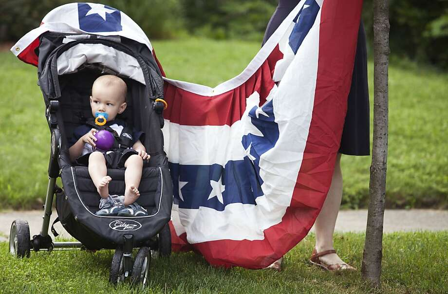 Leo Duncan sits in his stroller as his mother, Amy Duncan, sets up a flag before the start of the annual Hollyhock Lane Independence Day Parade in the Ottawa Hills neighborhood of Grand Rapids, Mich., Thursday, July 4, 2013. The parade a tradition in the neighborhood since 1934. Photo: Lauren Petracca, Associated Press