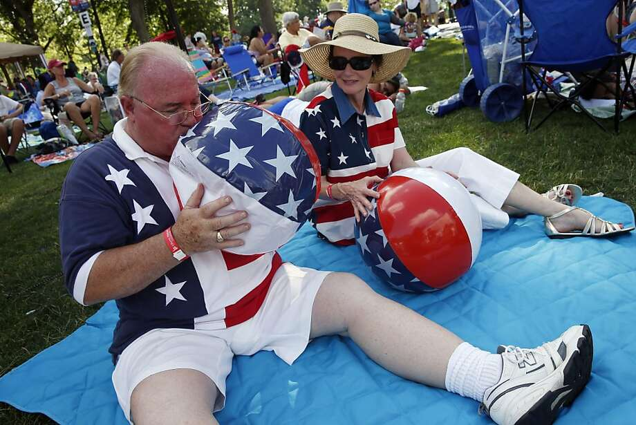 Ray Mutter, left, and Deb Thomas, both of Harrisonburg, Va., blow up beach balls while waiting the start of the Boston Pops Fourth of July Concert at the Hatch Shell in Boston, Thursday, July 4, 2013. Photo: Michael Dwyer, Associated Press
