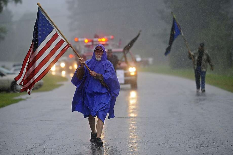 Neil Thrasher carries the American flag at the start of a Fourth of July parade in the Meeksville community in Pike County, Ala., Thursday, July 4, 2013. Photo: Thomas Graning, Associated Press