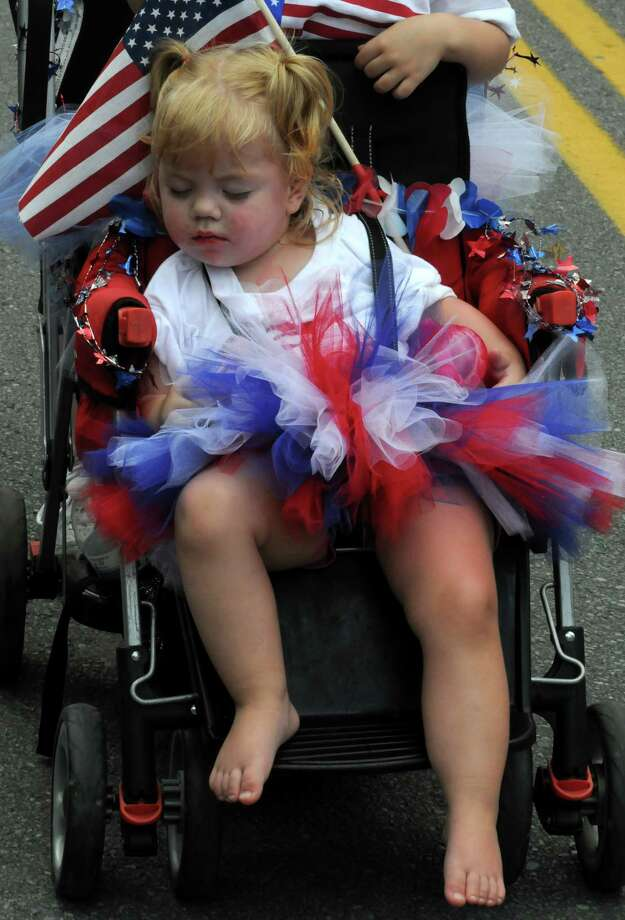 Two-year-old Dahlia Merchant of Saratoga sits sound asleep as she is pushed by her sister Helena Merchant in the Saratoga Springs 4th of July Parade on Thursday July 4, 2013 in Saratoga Springs, N.Y. (Michael P. Farrell/Times Union) Photo: Michael P. Farrell / 00023042A
