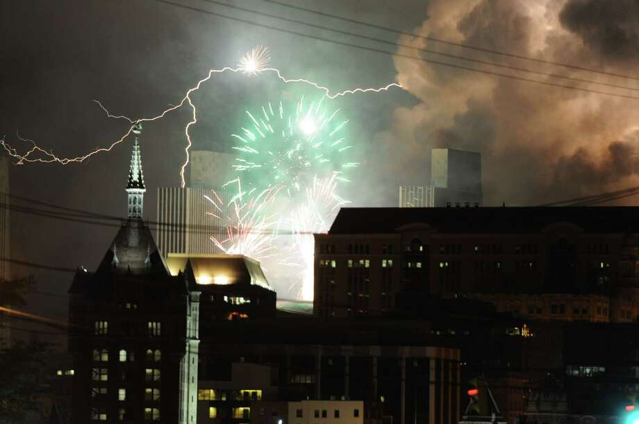 Fireworks and lightning light up the sky over Albany during New York State?s 4th of July Celebration Presented By Price Chopper at the Empire State Plaza. This photo was taken from the streets of Rensselaer, N.Y. Photo: WILL WALDRON / 00023016A