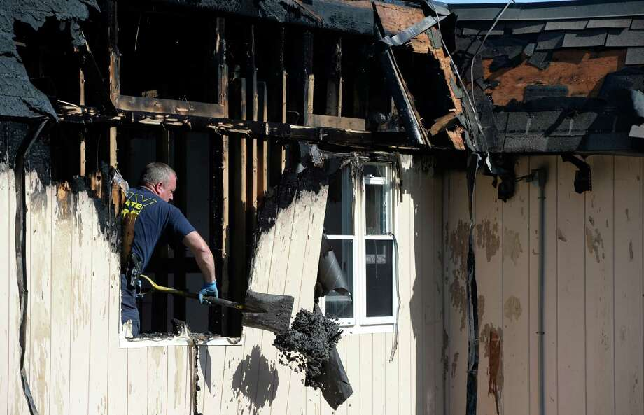 A State Fire investigator removes debris from the scene of an early morning fire July 5, 2013,  at the Troy Housing Authority Apartments at 111 Eddy's Lane in Troy, N.Y.  A number of people were forced from their homes as a result of the fire.   (Skip Dickstein/Times Union) Photo: SKIP DICKSTEIN
