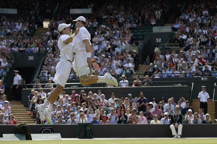 TOPSHOTS US players Bob Bryan (R) and Mike Bryan (L) do their trademark chest bump celebration after beating India's Rohan Bopanna and France's Edouard Roger-Vasselin in their men's doubles semi-final match on day ten of the 2013 Wimbledon Championships tennis tournament at the All England Club in Wimbledon, southwest London, on July 4, 2013. AFP PHOTO / ADRIAN DENNIS  -  RESTRICTED TO EDITORIAL USEADRIAN DENNIS/AFP/Getty Images ORG XMIT: 3435 Photo: ADRIAN DENNIS, Getty / AFP