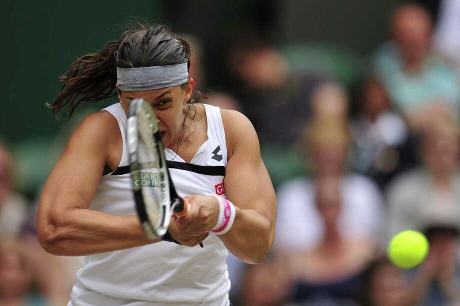 TOPSHOTS France's Marion Bartoli returns against Belgium's Kirsten Flipkens during their women's singles semi-final match on day ten of the 2013 Wimbledon Championships tennis tournament at the All England Club in Wimbledon, southwest London, on July 4, 2013.  AFP PHOTO / GLYN KIRK  -  RESTRICTED TO EDITORIAL USEGLYN KIRK/AFP/Getty Images ORG XMIT: 3296 Photo: GLYN KIRK, Getty / AFP