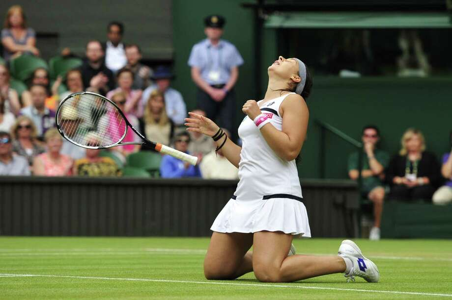 TOPSHOTS France's Marion Bartoli celebrates beating Belgium's Kirsten Flipkens during their women's singles semi-final match on day ten of the 2013 Wimbledon Championships tennis tournament at the All England Club in Wimbledon, southwest London, on July 4, 2013. Bartoli won 6-1, 6-2.  AFP PHOTO / GLYN KIRK  -  RESTRICTED TO EDITORIAL USEGLYN KIRK/AFP/Getty Images ORG XMIT: 3314 Photo: GLYN KIRK, Getty / AFP