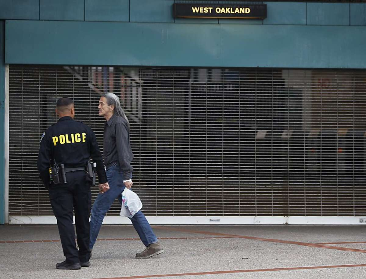 A BART police officer assists a man in front of the West Oakland station in Oakland, Calif. on Friday, July 5, 2013. BART service will resume at 3pm Friday after union employees agreed to suspend their strike for 30 days while negotiations continue.