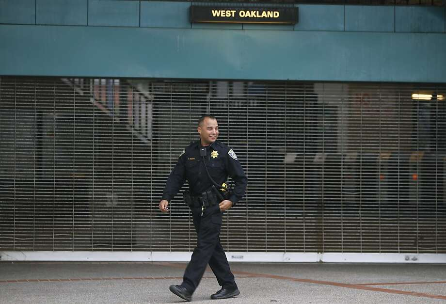 A BART police officer patrols in front of the West Oakland station in Oakland, Calif. on Friday, July 5, 2013. BART service will resume at 3pm Friday after union employees agreed to suspend their strike for 30 days while negotiations continue. Photo: Paul Chinn, The Chronicle