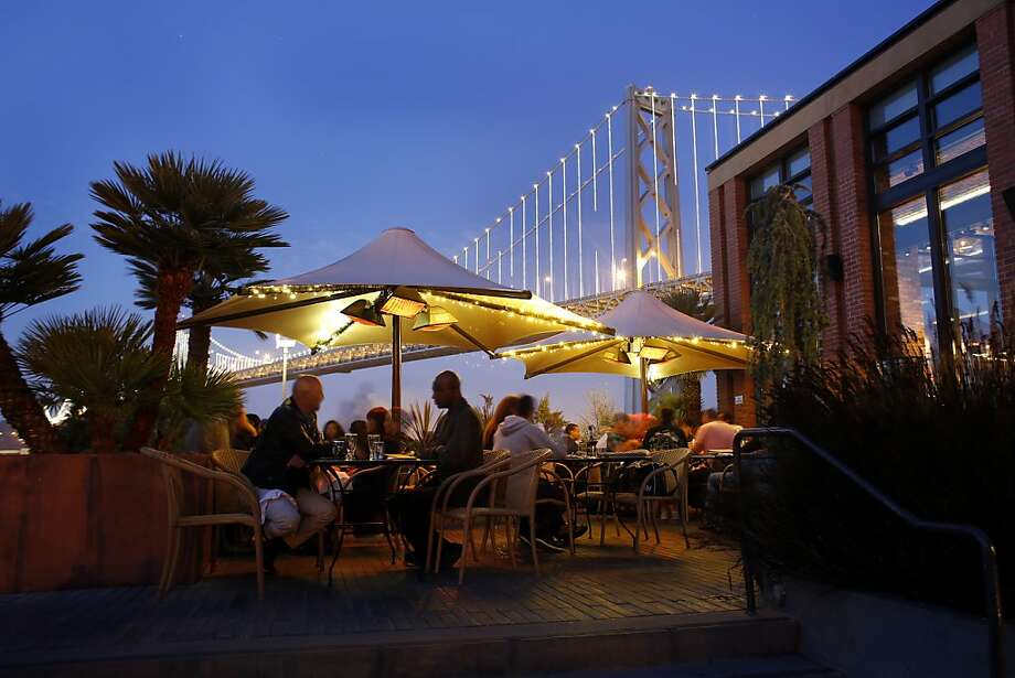 Diners gather at dusk at the Waterbar on the south end of the Embarcadero with views of the Bay Bridge. Owner Pat Kuleto says the waterfront is the place to be. Photo: Ian C. Bates, The Chronicle