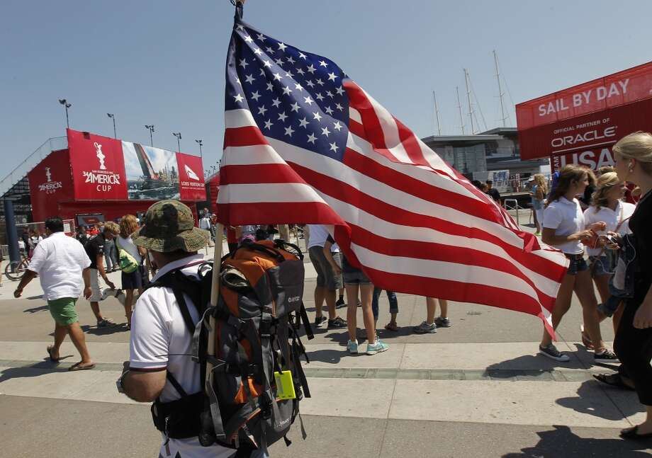 Ramil Pascual, of San Francisco, totes an american flag in front of the newly opened America's Cup Park in San Francisco, Calif., on Thursday July 4, 2013. America's Cup Park opens along the Embarcadero launching the first day of the summer of racing.