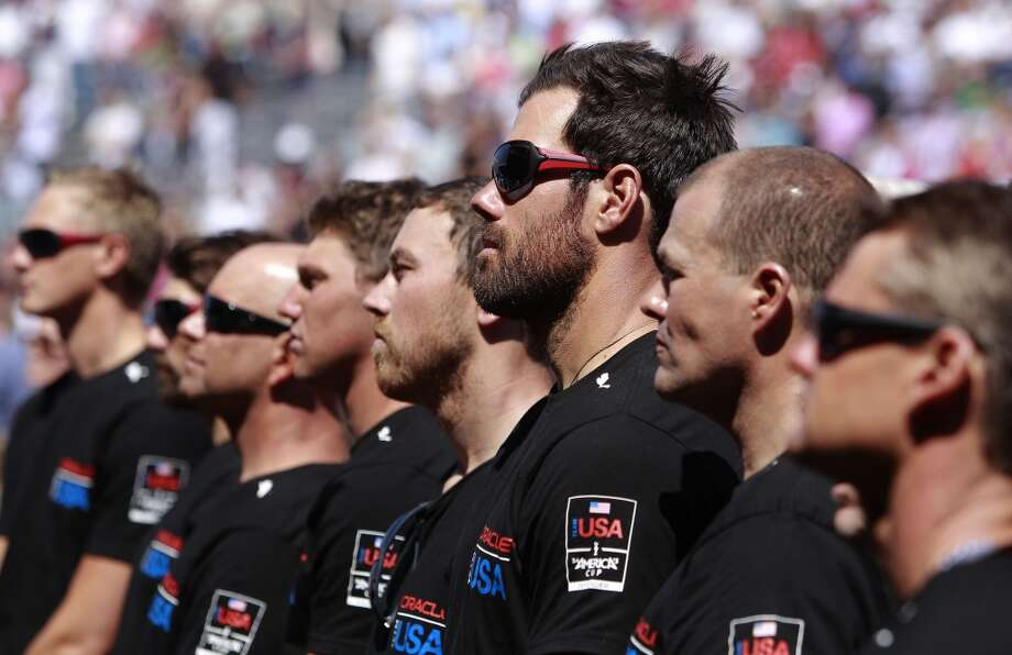 Oracle Team USA crew members, including Shannon Falcone, (center) during the opening day ceremony at America's Cup Park on Thursday July 4, 2013, in San Francisco, Calif., watch a video to remember Artemis crew member Bart Simpson who lost his life during a practice sail on the Bay. America's Cup Park opens along the Embarcadero at Pier 23 launching the first day of the summer of racing.