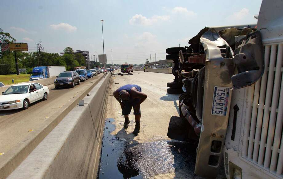 A man looks at the front of an 18-wheeler after it overturned causing an accident on the westbound North Loop near T.C. Jester, Friday, July 5, 2013, in Houston. Photo: Cody Duty, Houston Chronicle / © 2013 Houston Chronicle