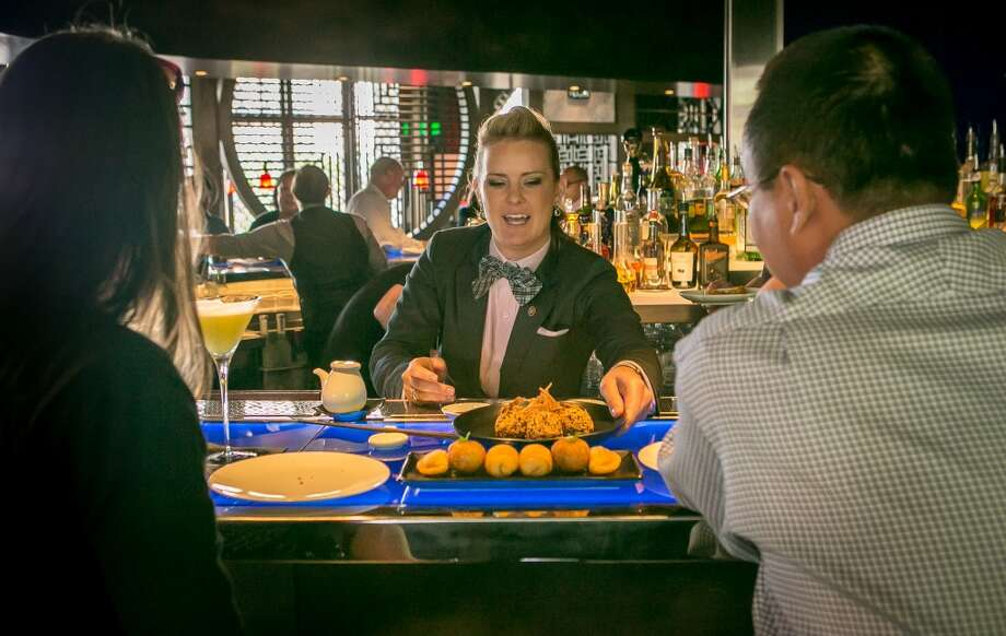 Bartender Jessamine McLellan serves a dim sum platter to customers.