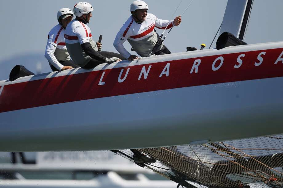 Members of Luna Rossa Piranha lean toward starboard as their boat stand aloft in water near the finish line during a fleet race in America's Cup World Series in San Francisco Bay, Calif. on Sunday, Aug. 26, 2012.