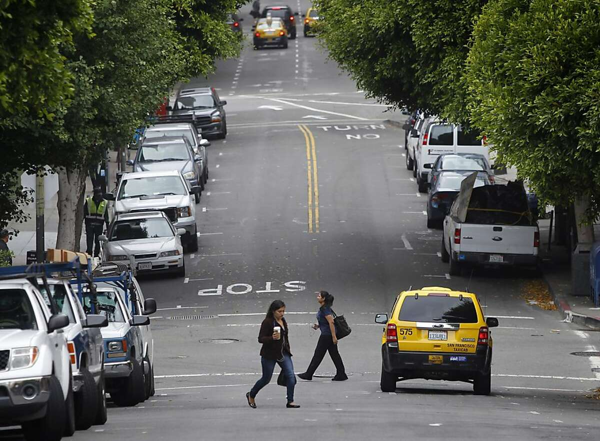 Pedestrians cross Montgomery Street where it intersects with Jackson Street in San Francisco, Calif. on Friday, July 5, 2013. A small wooden footbridge once stood where the intersection now is, providing a crossing over a small lagoon for inhabitants during the Gold Rush era.