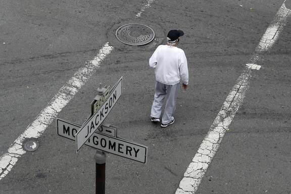 A man crosses Montgomery Street where it intersects Jackson Street in San Francisco, Calif. on Friday, July 5, 2013. A small wooden footbridge once stood where the intersection now is, providing a crossing over a small lagoon for inhabitants during the Gold Rush era.