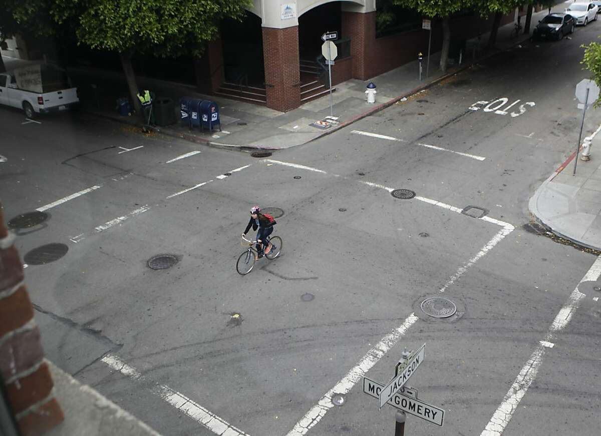 A bicyclist rides through the intersection of Jackson and Montgomery streets in San Francisco, Calif. on Friday, July 5, 2013. A small wooden footbridge once stood where the intersection now is, providing a crossing over a small lagoon for inhabitants during the Gold Rush era.