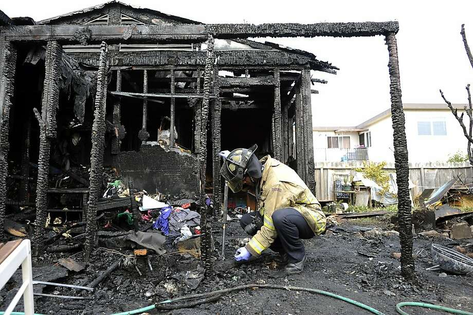 Richmond fire Inspector Eric Govan sifts through the ashes of a blaze that killed two people in a converted garage. Photo: Michael Short, Special To The Chronicle