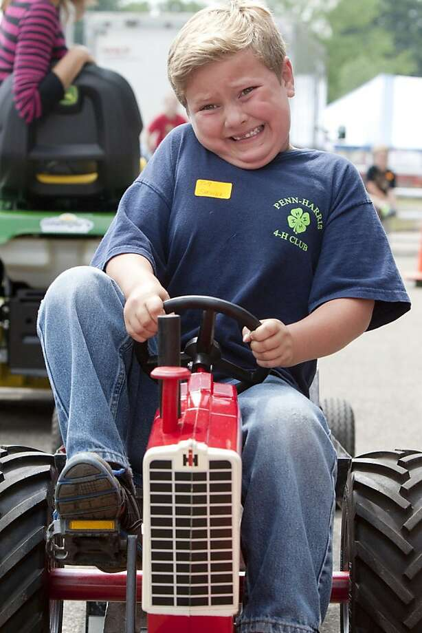 Go, Gabe! Six-year-old Gabe Spencer strains to drag a 250-pound sled during the mini-pedal tractor pull at the St. Joseph County 4-H Fair in South Bend, Ind. Photo: James Brosher, Associated Press