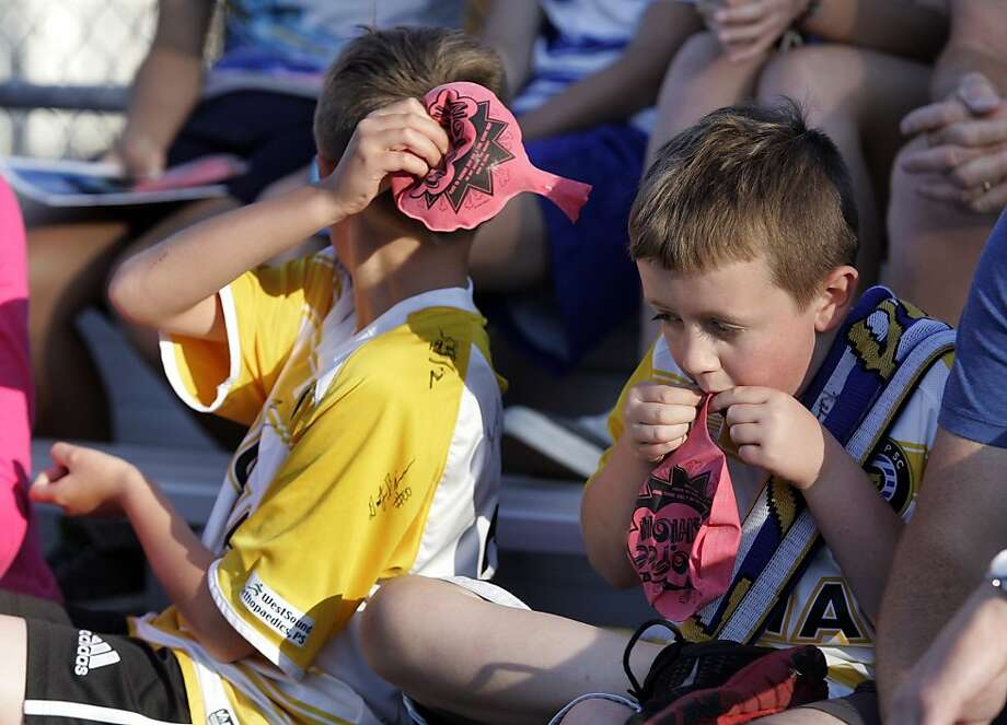 "Suddenly vuvuzelas don't seem so bad:Brothers Gage Kelley (left) squeezes out a Bronx cheer as brother Gabriel reloads at the Kitsap Pumas soccer game at Gordon Field in Bremerton, Wash. The team's Whoopee Cushion giveaway was billed as ""Create Your Own Fireworks."" Photo: Larry Steagall, Associated Press"