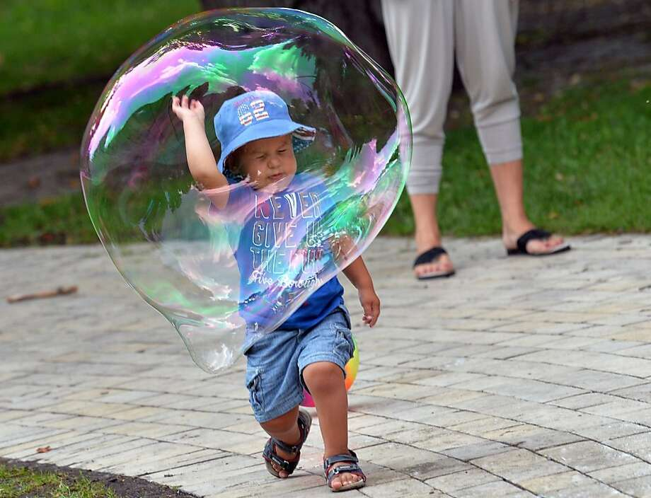 The bubble boy:In Kiev, a soap bubble swallows a child. Photo: Sergei Supinsky, AFP/Getty Images