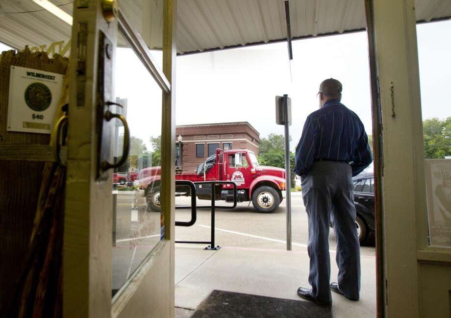 Conrad Wolfman watches from his storefront as a truck that hauls equipment for TransCanada's Keystone XL project drives through downtown Winnsboro, Thursday, Oct. 25, 2012, in Wood County. (Cody Duty / Houston Chronicle)