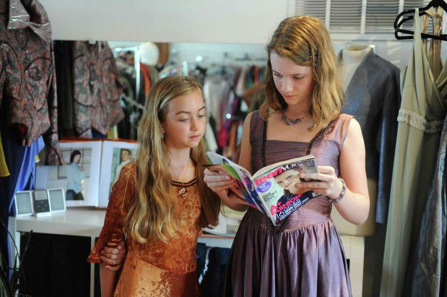 Hazel Foley, 9, and Olivia Foley, 13, read a copy of Teen Vogue at the Fairfield workshop of their mother, dress designer Jennifer Butler. Photo: Autumn Driscoll / Connecticut Post