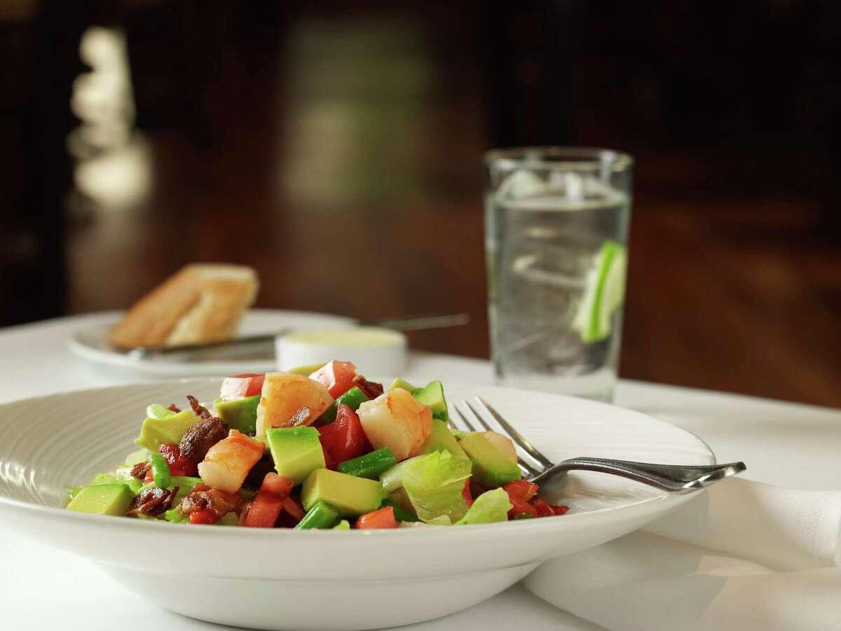 The Louis Gigi Delmaestro Salad consists of shrimp, green beans, tomato, onion, bacon, iceberg lettuce, roasted pepper, egg and avocado.