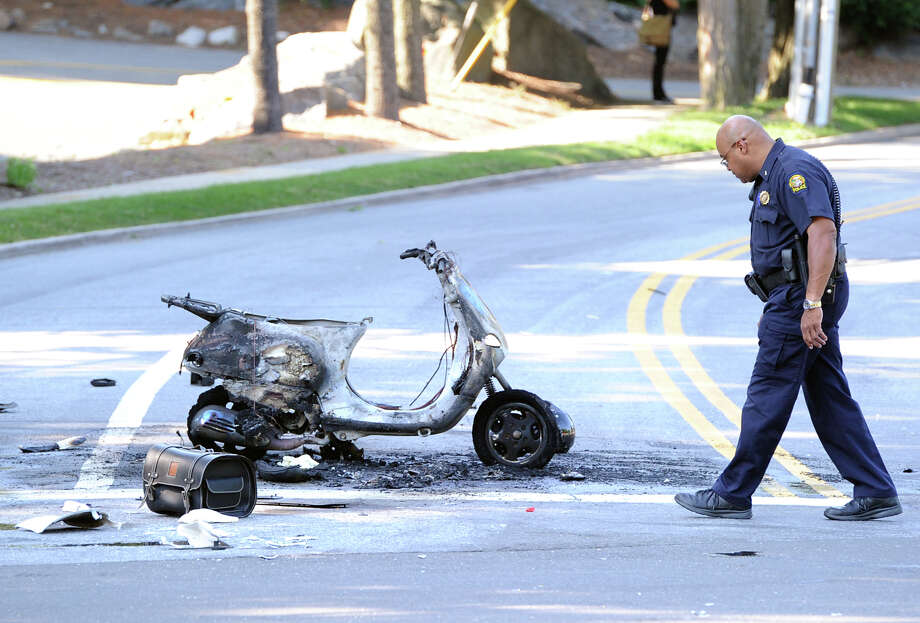 Greenwich police investigate the scene of an accident in which a moped was incinerated at the corner of Valley Drive and West Putnam Avenue in Western Greenwich, Friday, July 5, 2013. Photo: Bob Luckey / Greenwich Time