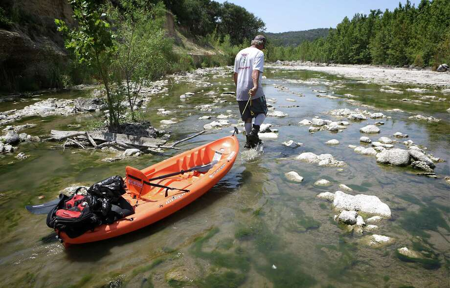 Guide Mike Crandall of Wally's Watersports in Mico pulls his kayak through shallow waters at Diversion Lake which starts just below Medina Lake Dam, on Thursday, July 4, 2013. Drought conditions have severly impacted Diversion Lake as seen on Monday, July 1, 2013. Until April, the Diversion Lake water level was maintained by releases of water from Medina Dam and went ont to flowinto the Medina River and supply San Antonio. Photo: Bob Owen, San Antonio Express-News / © 2012 San Antonio Express-News