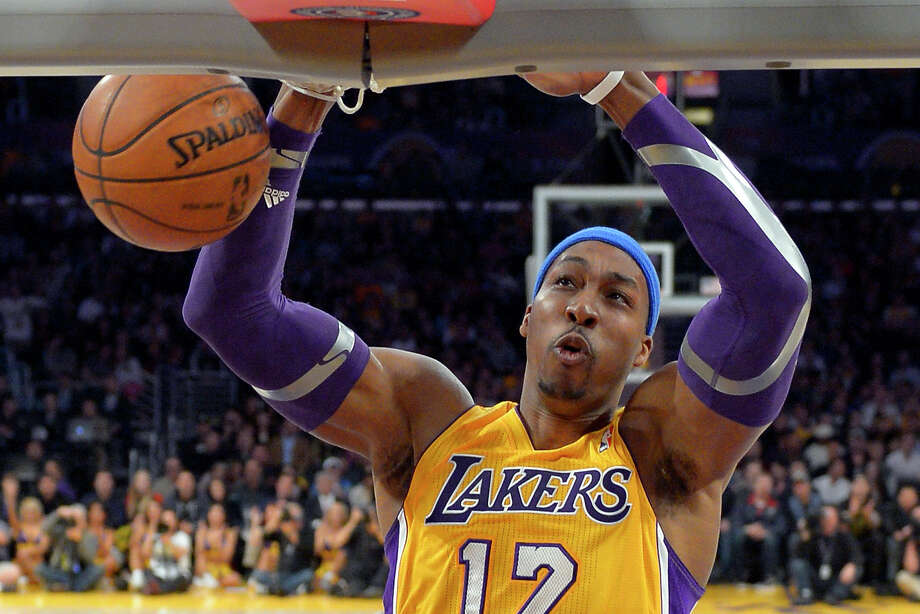 FILE - In this Jan. 25, 2013 file photo, Los Angeles Lakers center Dwight Howard dunks during the first half of their NBA basketball game against the Utah Jazz, in Los Angeles. Chris Paul is staying in Los Angeles; Dwight Howard could be leaving. NBA free agency opens, with Paul sticking with the Clippers and Howard exploring his options before deciding on his future with the Lakers. (AP Photo/Mark J. Terrill, File) Photo: Mark J. Terrill, STF / AP