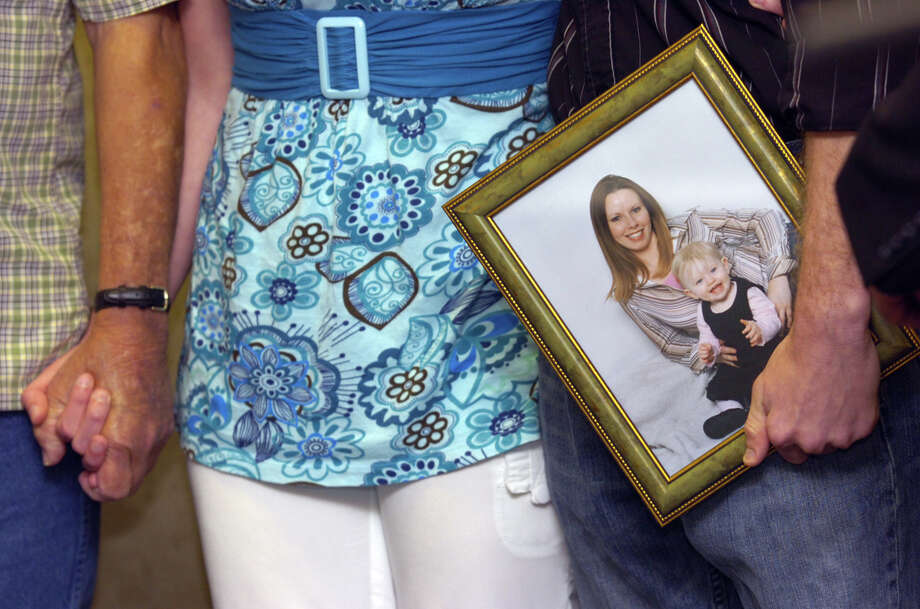 """Family members of Bridgette Gearen, seen with her daughter in a pictures, hold hands during a press conference Tuesday, July 24, 2007, at the Galveston County Sheriff's Office in Galveston.  Friday marks four years since the violent rape and killing of Bridgette Gearen, an Orange single mom. Though no arrests have been made, Galveston County Lt. Tommy Hansen calls the case """"extraordinarily active"""" and believes charges may be filed within the next year. Enterprise file photo Photo: File / Beaumont"""