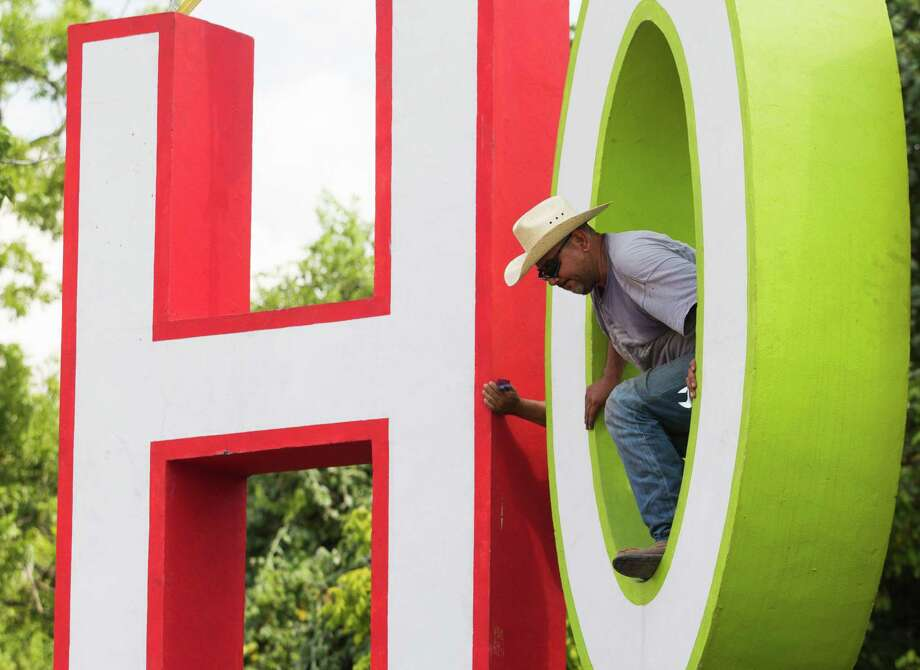 Jesus Flores walks through the O on David Adickes latest artwork. Photo: J. Patric Schneider, Freelance / © 2013 Houston Chronicle