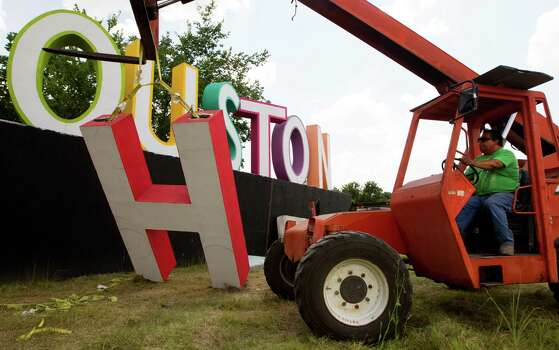 Filipe Torres raises the H on David Adickes latest artwork, a 30 foot tall I heart Houston sign, near Interstate 10 and Patterson on Tuesday, July 2, 2013, in Houston.  Photo: J. Patric Schneider, Freelance / © 2013 Houston Chronicle