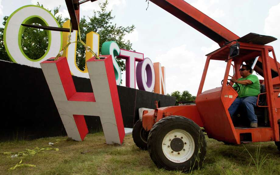Filipe Torres raises the H on David Adickes latest artwork, a 30 foot tall I heart Houston sign, near Interstate 10 and Patterson on Tuesday, July 2, 2013, in Houston. ( J. Patric Schneider / For the Chronicle ) Photo: J. Patric Schneider, Freelance / © 2013 Houston Chronicle