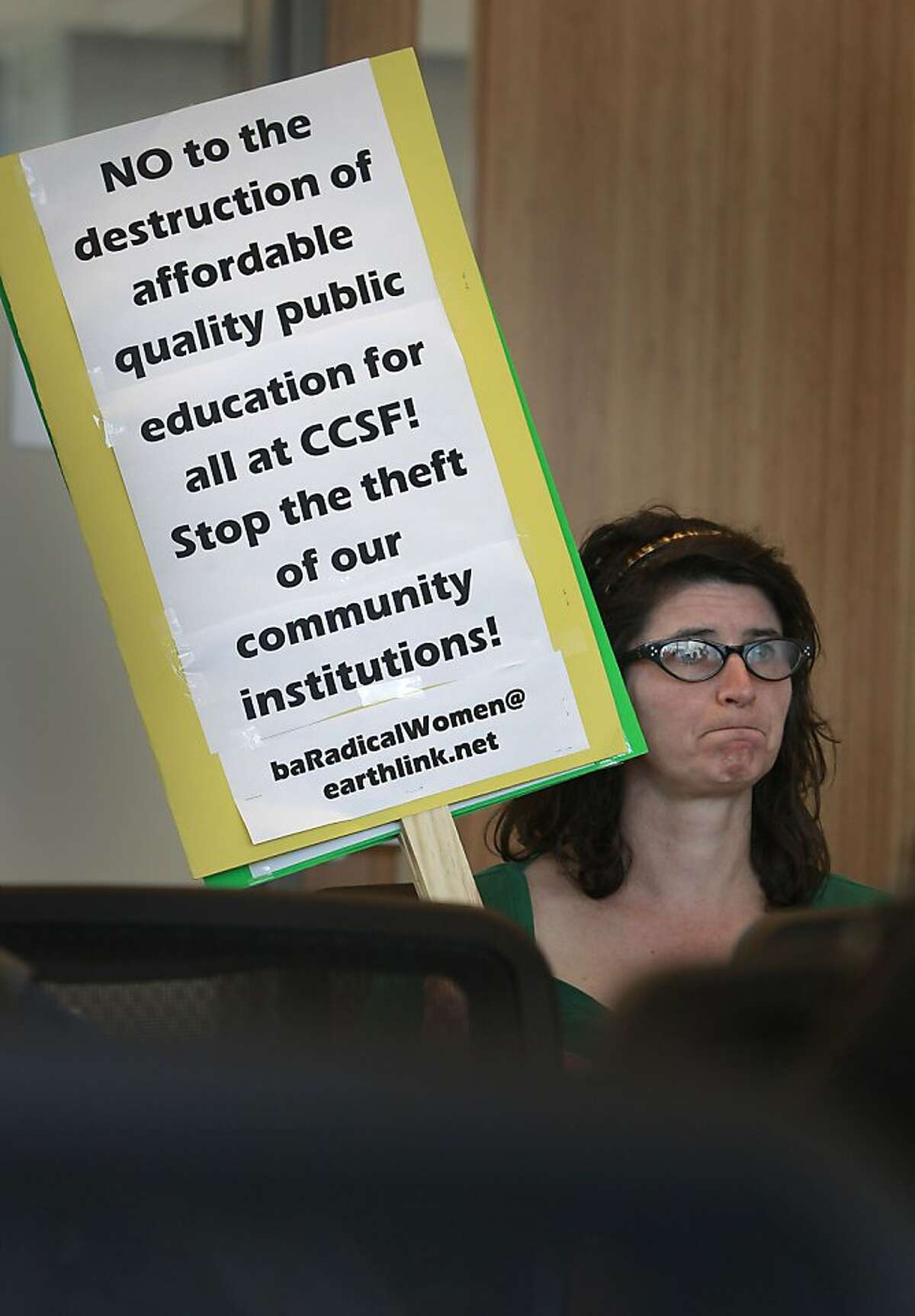Community supporter and former CCSF student Toni Mendocino holds a sign as she listens to the panel made up of members of the Save CCSF Coalition ?' which represents faculty, students, staff, and community members. They are rejecting the legitimacy of the Accrediting Commissions' decision to terminate the school's accreditation as they hold a press briefing at the Chinatown/North Beach campus of CCSF in San Francisco, Calif., on Friday July 5, 2013.