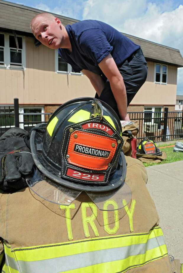 Tom Bennett, one of the ten new Troy firefighters, takes off his gear at the Martin Luther King Apartments where a fire damaged many homes on Friday, July 5, 2013 in Troy, N.Y. (Lori Van Buren / Times Union) Photo: Lori Van Buren / 00023049A