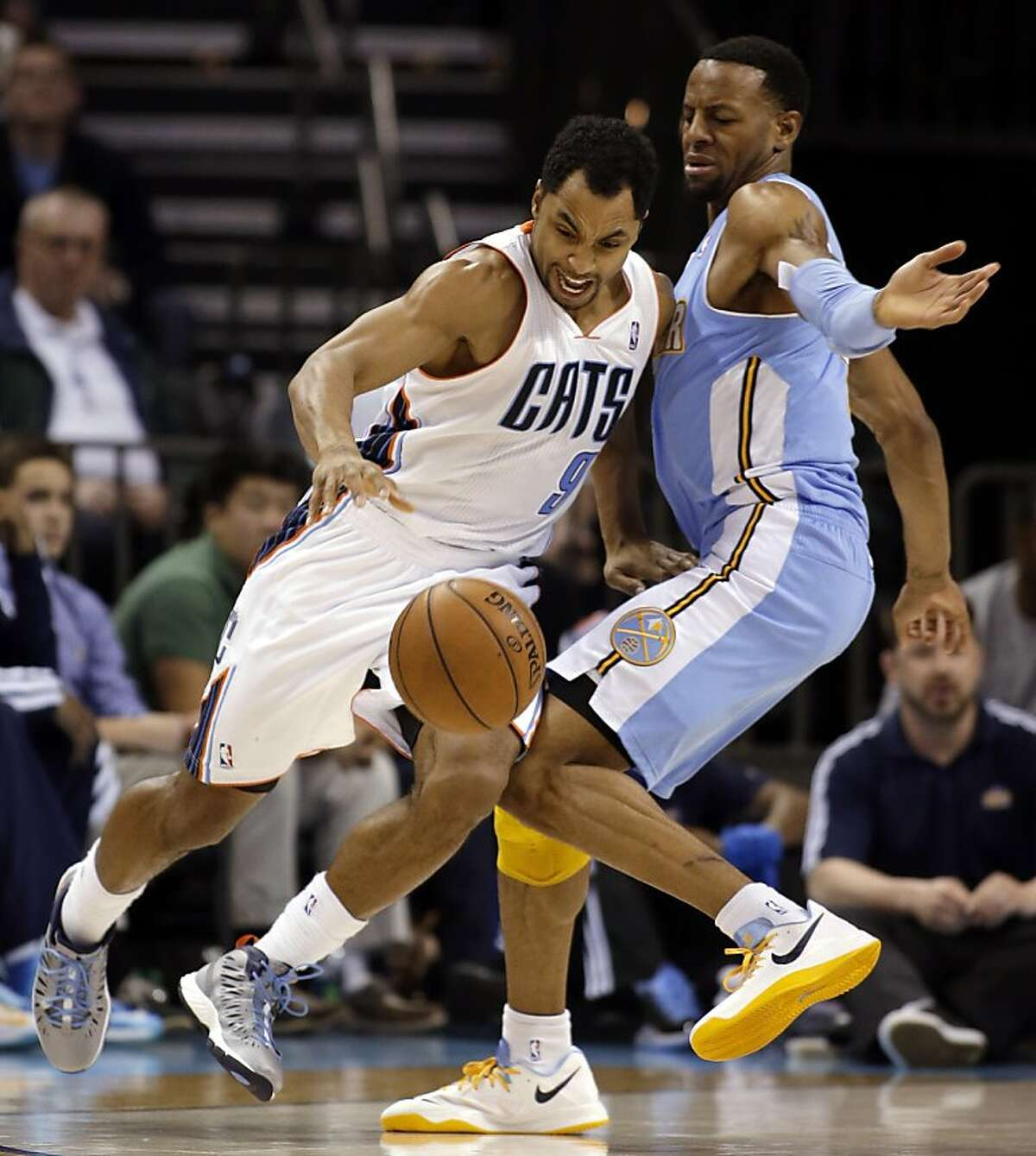 Charlotte Bobcats' Gerald Henderson (9) grimaces as he tries to get around Denver Nuggets' Andre Iguodala during the second half of an NBA basketball game in Charlotte, N.C., Saturday, Feb. 23, 2013. The Nuggets won 113-99. (AP Photo/Bob Leverone)