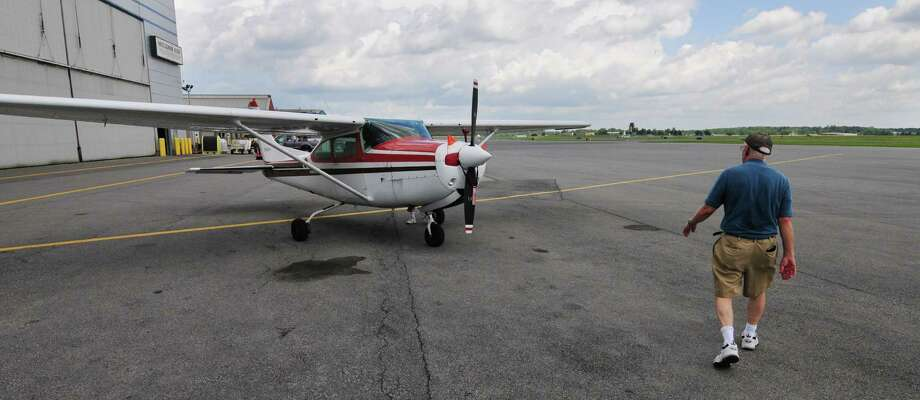 Pilot Ken Haefner of Schenectady walks to the Cessna 182 which he flew from Albany to Glens Falls and back to celebrate his 80th birthday Friday morning, July 5, 2013, at Albany International Airport in Colonie, N.Y. Haefner became a card-carrying member of UFO, otherwise known as United Flying Octogenarians.  He belongs to a local flying club called the Condair Flyers. The 75 members jointly own five airplanes, including the Cessna which Haefner flew Friday. (Will Waldron/Times Union) Photo: WW / 00023068A