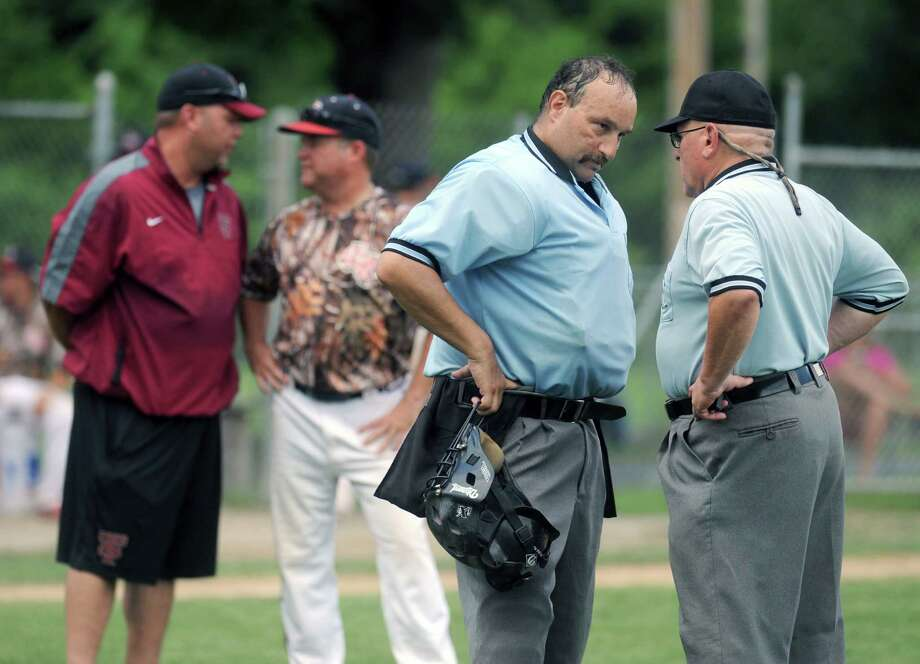 Umpires and opposing coaches have discussions about a reversed call during the South Troy Dodgers against the Frozen Ropes of Texas in the 2013 Connie Mack World Series qualifier on Friday July 5, 2013 in Troy, N.Y. (Michael P. Farrell/Times Union) Photo: Michael P. Farrell / 00023073A