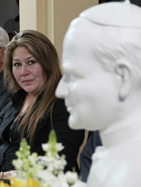 Floribeth Mora, during a press conference Friday at the Archbishop's office in San Jose, Costa Rica, eyes a bust of Pope John Paul II while giving her account of a miracle attributed to him. Photo: Associated Press