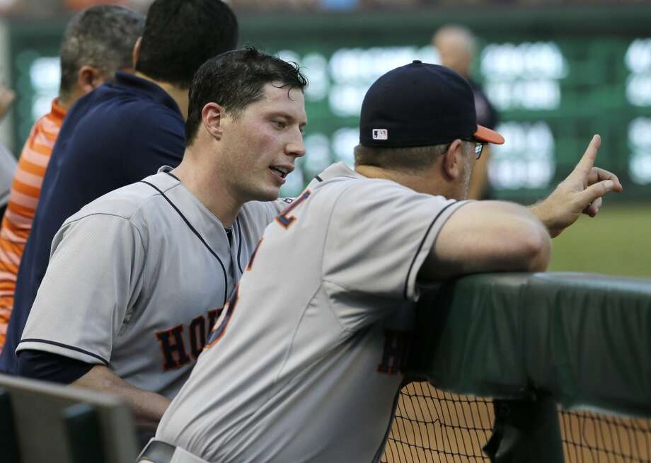 Astros starting pitcher Lucas Harrell, left, talks with pitching coach Doug Brocail, right, in the dugout during the bottom of the second inning.