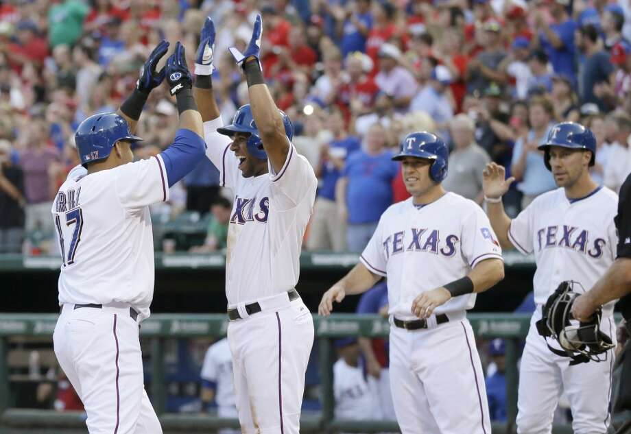 Nelson Cruz, left, is congratulated at the plate by Elvis Andrus, from second left, Ian Kinsler and David Murphy who scored on the Cruz grand slam.