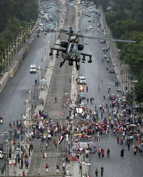 A military attack helicopter flies over a street near the presidential palace in Cairo. The city saw the nation's most widespread street violence since the early days of the 2011 revolution. Photo: Hassan Ammar / Associated Press