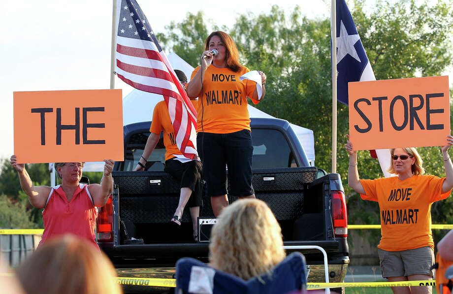 Gina Turner leads a chant from her perch on a pickup truck as homeowners gather at the Falcon Ridge subdivision pool  on July 5, 2013 to organize support for their fight to change Walmart's plan to build a store near a school in their community. Photo: For The San Antonio Express-News