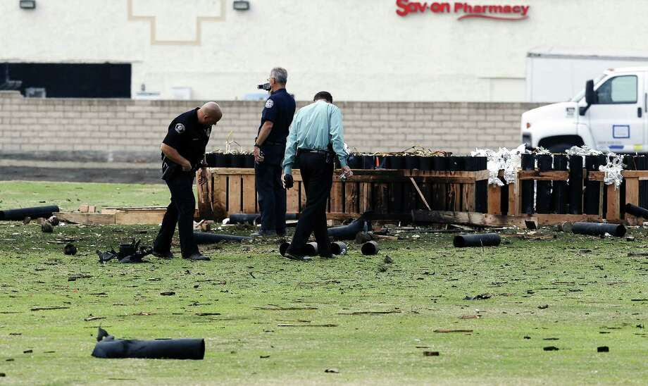 Police investigate the site in Simi Valley, Calif., where more than two dozen people were injured during a fireworks display. Some witnesses said a rack of fireworks fell over. Photo: Nick Ut / Associated Press